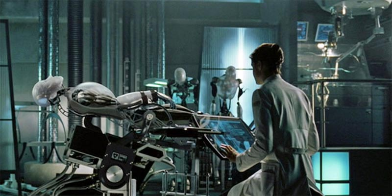Roboticienne sur son poste de travail et contrôlant un robot humaniforme